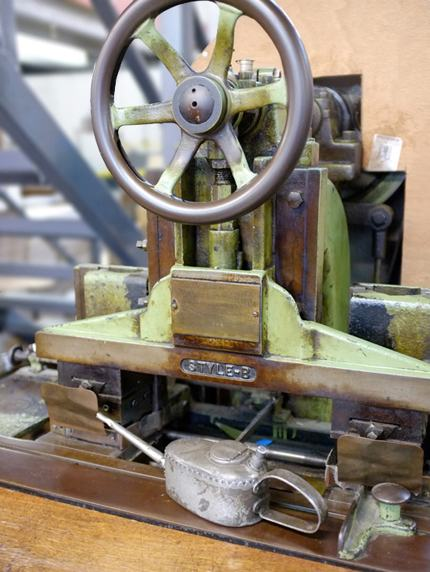 This is our oldest machine, made in 1908. It cuts paper to the correct shape so it can be folded around the box