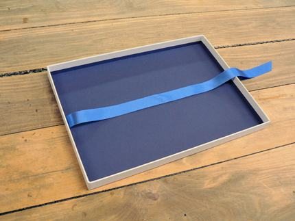 Tray with ribbon pull for removing contents